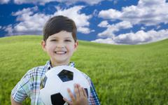 Cute Smiling Young Boy Holding Soccer Ball on Green Grass in the Park. - stock photo