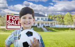 Boy Holding Ball In Front of House and Sale Sign - stock photo