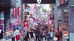 People walk and shop along the Takeshita Street in Harajuku, Tokyo, Japan Stock Footage