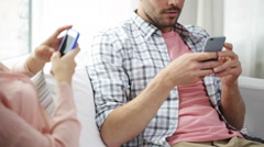 Couple with smartphones texting at home Stock Footage
