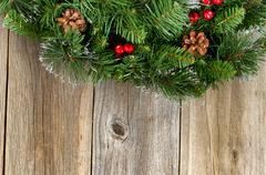 Christmas border with decorative wreath on rustic wooden boards - stock photo
