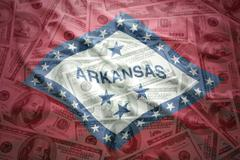 colorful waving arkansas state flag on a american dollar money background - stock photo