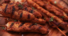 Barbecued bacon twists and chicken skewers on a wooden board Stock Footage