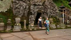 Two old woman come out from gaping mouth cave, giant face rock, Goa Gajah Stock Footage