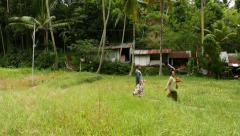 Indonesian pair come across grass field, against hovel and tropical forest Stock Footage