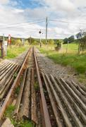 Narrow gauge railway or railroad track converging into distance - stock photo