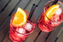 close-up of view of glasses of spritz aperitif aperol red cocktail with orang - stock photo