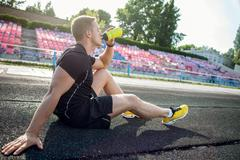 Handsome young male runner is relaxing after training - stock photo