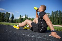 Attractive young male runner is very thirsty - stock photo