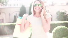 Happy young woman speaking over the phone while walking with shopping bags in th Stock Footage