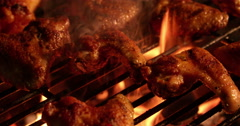 Spicy chicken wings grilling over glowing coals of a barbecue Stock Footage