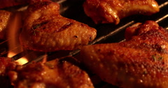 Chicken wings being grilled over glowing coals at a barbecue - stock footage