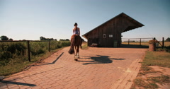 Girl on a lush green farm riding her horse Stock Footage