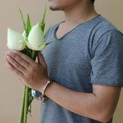 young man in handcuffs and lotus in hand - stock photo