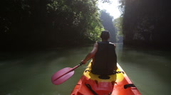 Old man drifts on kayak down river along sunlit canyon Stock Footage