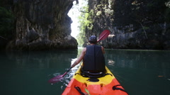 Man backside view rows on kayak out to sea Stock Footage