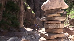 Stone pyramid and family playing on a valley river with stones in the background Stock Footage