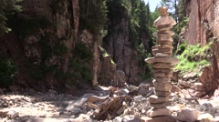 Stone pyramid and family playing with stones and water in nature Stock Footage