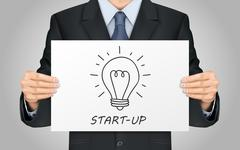 businessman holding start-up poster - stock illustration