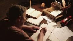 Old Man Writes At The Table Stock Footage