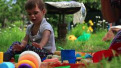 Little boy playing with toys at a garden. dolly shot Stock Footage