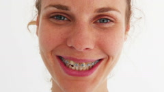 Young redhead woman with braces smiling at camera. Stock Footage