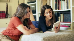 Friends relaxing at home and reading book together Stock Footage