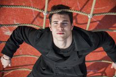 Full length of serious 20s man on climbling rope Stock Photos