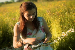 Girl smiling to the camera on the meadow and doing grommet Stock Footage