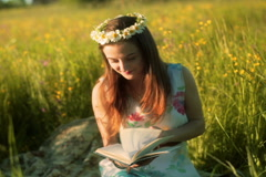 Girl wearing grommet and reading book on the meadow Stock Footage