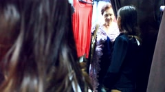 Young smiles woman trying on clothes in a clothing store In the locker room shop Stock Footage