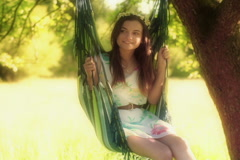 Happy girl sitting and swinging on hammock Stock Footage