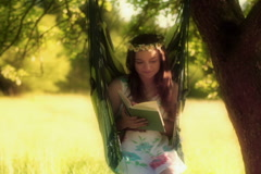 Girl reading book and smiling to the camera on hammock Stock Footage