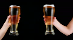 Clinking Beer Glasses on a Black Background - stock footage