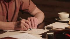 Old Man Writes At The Table - stock footage