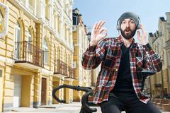 Cheerful young cyclist with headphones and cap Stock Photos