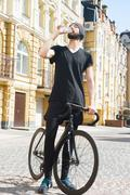 Cheerful young man is thirsty after cycling Stock Photos