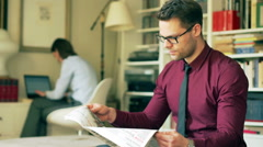 Businessman reading newspaper and woman working at home Stock Footage