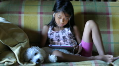 Young Asian Girl Enjoys Reading On Her Tablet Stock Footage