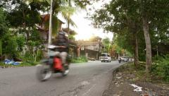 Low sunlight over village road, tropical forest around, traffic Stock Footage