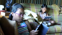 Young Asian Sisters Using Their Tablets In The Living Room Stock Footage