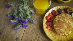 Overhead shot of gourmet breakfast of strawberries, orange juice and pancakes Stock Footage