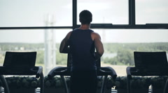Silhouette of man running on the treadmill and looking into the large window Stock Footage