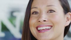 Attractive woman looks slightly past camera to laugh loudly - stock footage