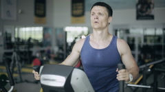 Handsome man at the gym exercising on the trainer machine Stock Footage