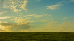 Horizon line, cloudy sky, green field, sunset Stock Footage