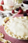 Uncooked Berry Pie on Counter with Ingredients - stock photo