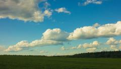 Horizon line, cloudy sky, green field Stock Footage