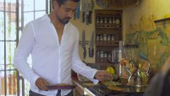 An attractive latino man cooks breakfast in a white linen shirt dolly shot Stock Footage
