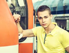 Handsome young man in polo shirt in front of train - stock photo